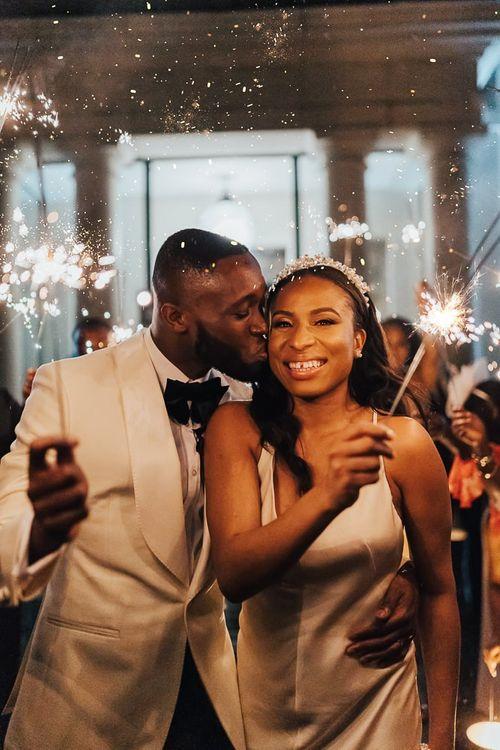 Groom kissing his bride during sparkler exit