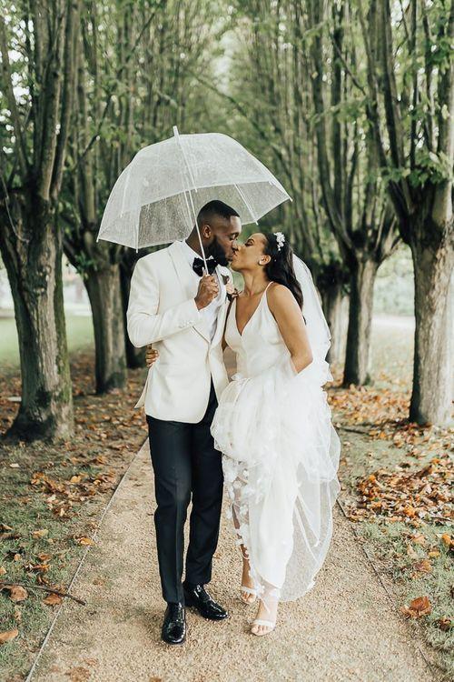 Bride and groom kissing under an umbrella at Coworth Park wedding