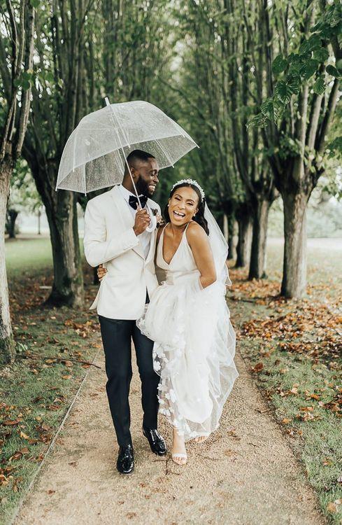 Stylish bride and groom laughing under an umbrella Autumn wedding