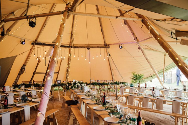 Rustic Tipi Decor with Trestle Tables & Edison Light Installation | Outdoor Wedding Ceremony & Tipi Reception Planned by Benessamy Events | Red on Blonde Photography
