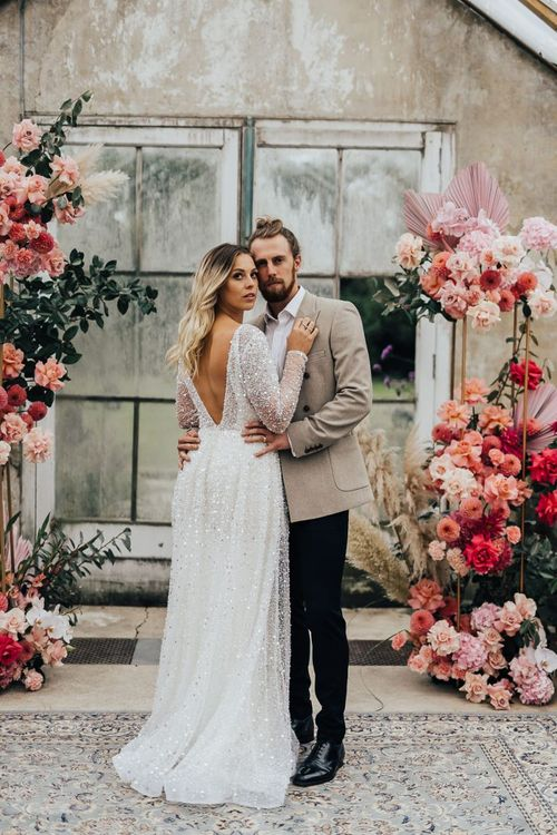 Bride in sparkle dress and groom in beige blazer surrounded by pink wedding flowers