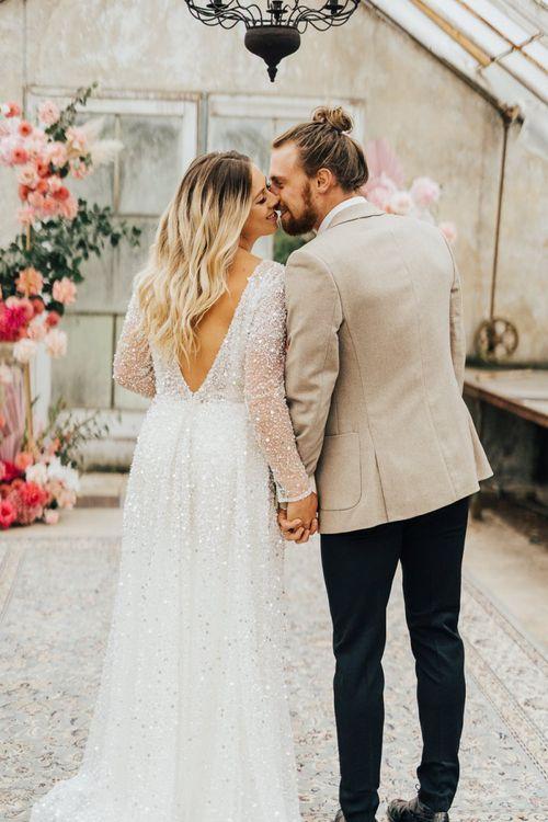 Bride in sequin wedding dress and groom in beige blazer holding hands