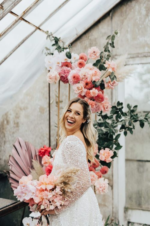 Laughing bride holding her pink bouquet