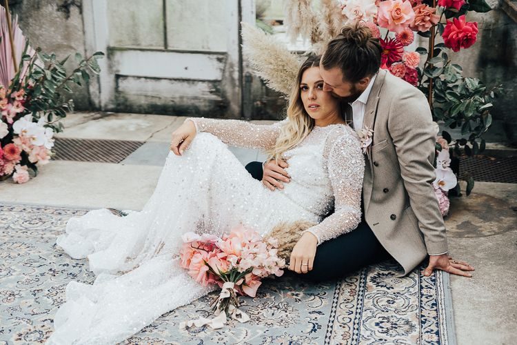 Bride and groom embracing on the floor on an ornate rug