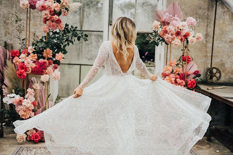 Bride in sparkling wedding dress twirling
