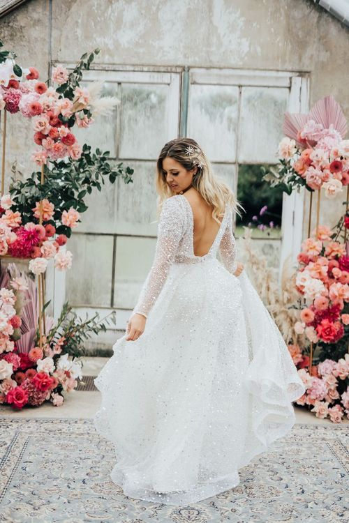 Bride in sparkling wedding dress standing in a conservatory with pink colour scheme