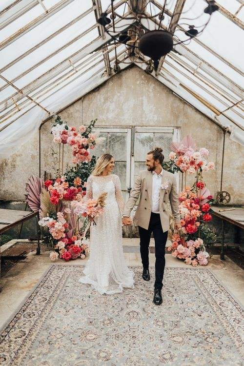 Bride and groom standing in front of a flower arrangement in pink colour scheme