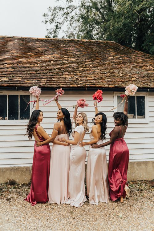 Bridesmaids in different pink dresses holding up their bouquets