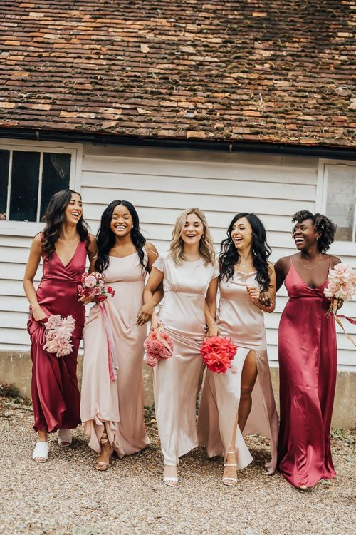 Bridesmaids walking together arm in arm in different pink dresses
