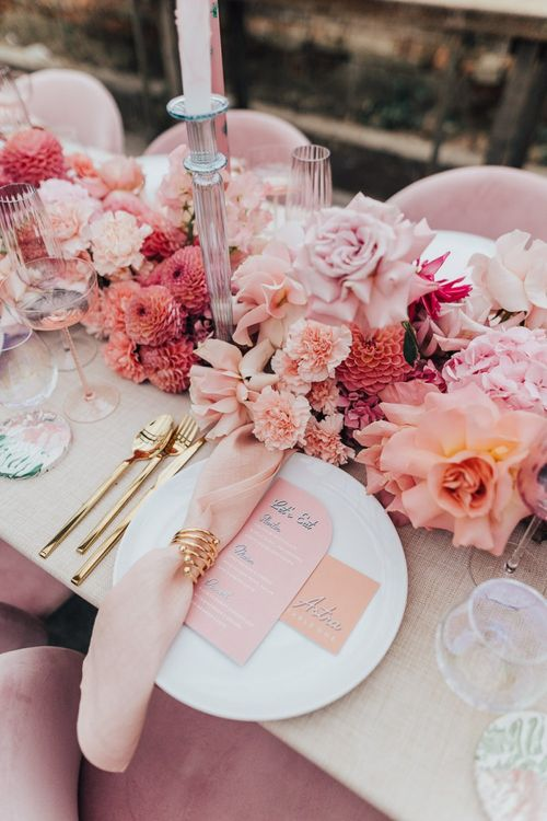 Intimate table scape setting with floral centrepiece, gold cutlery and matching stationery
