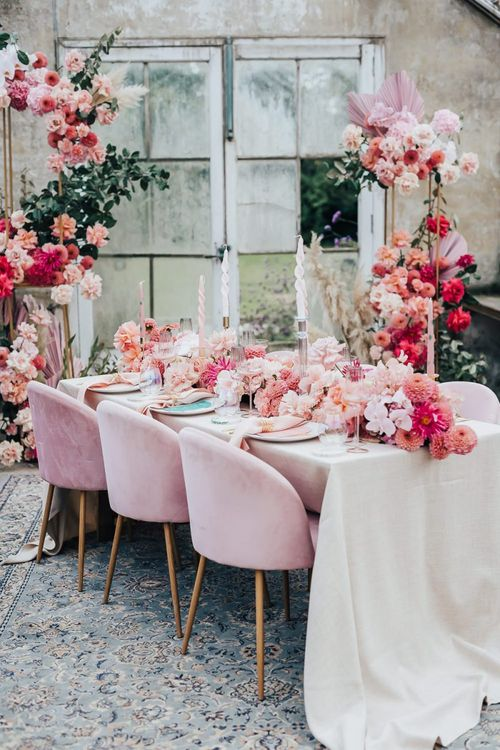 Pink colour scheme tablescape styling with velvet chairs, floral table runner and linens