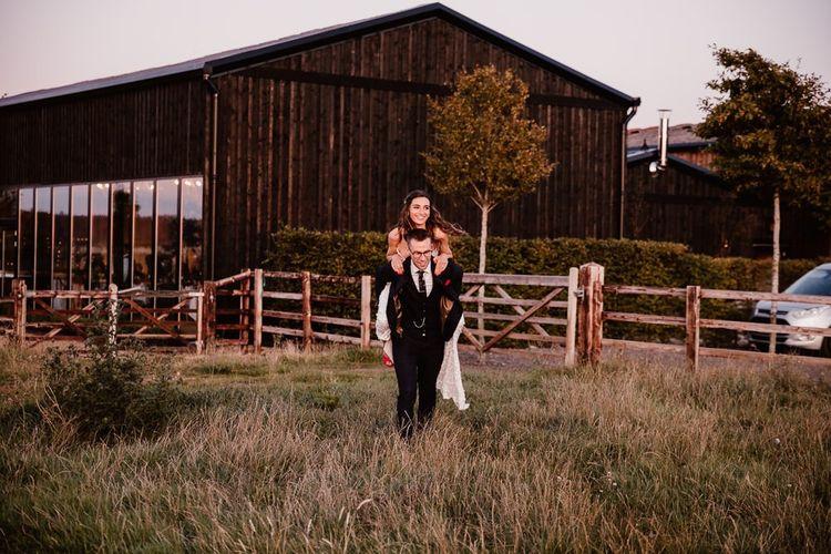 Groom Give Bride Piggy Back Through Field