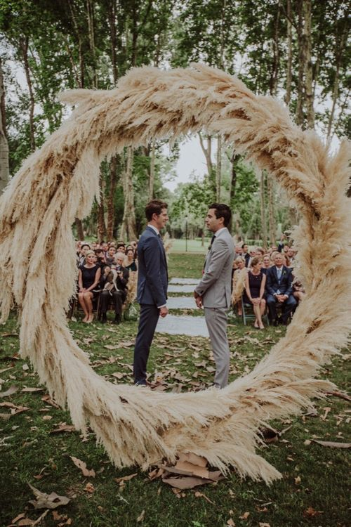 Outdoor Wedding Ceremony | Two Grooms in Grey Suits | Pampas Grass Moon Gate | Woodland Wedding at Sa Farinera de Sant LLuis Wedding Venue, Catalan Empordà, Spain | Planned & Styled by Mille Papillons | HUMà06 Photography | HUMà06 Photography