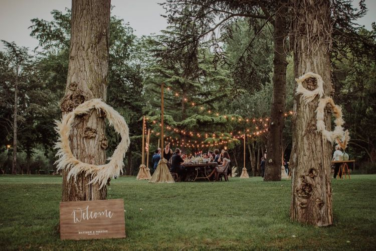 Pampas Grass Hoops & Wooden Welcome Sign Wedding Decor | Outdoor Woodland Wedding at Sa Farinera de Sant LLuis Wedding Venue, Catalan Empordà, Spain | Planned & Styled by Mille Papillons | HUMà06 Photography | HUMà06 Photography