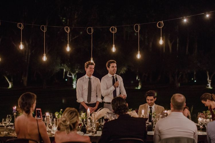 Two Grooms at Outdoor Wedding Reception Speeches with Festoon Lights | Woodland Wedding Ceremony at Sa Farinera de Sant LLuis Wedding Venue, Catalan Empordà, Spain | Planned & Styled by Mille Papillons | HUMà06 Photography | HUMà06 Photography