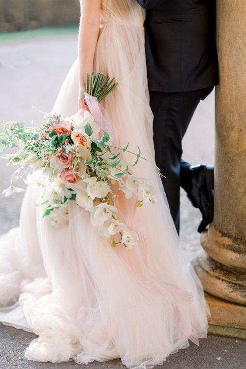 Peach and white wedding bouquet with orchids and roses