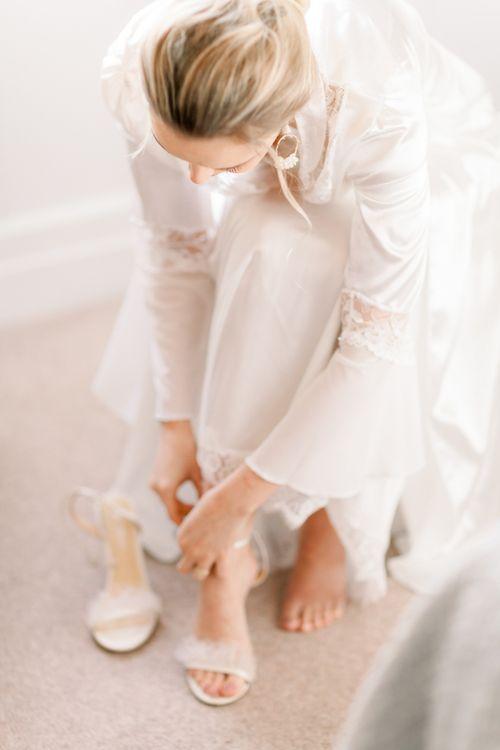 Bride putting on wedding shoes at Prestwold Hall wedding