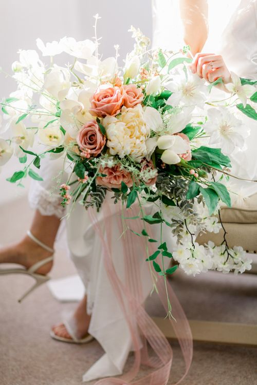 Romantic peach and cream wedding bouquet with roses and tulips