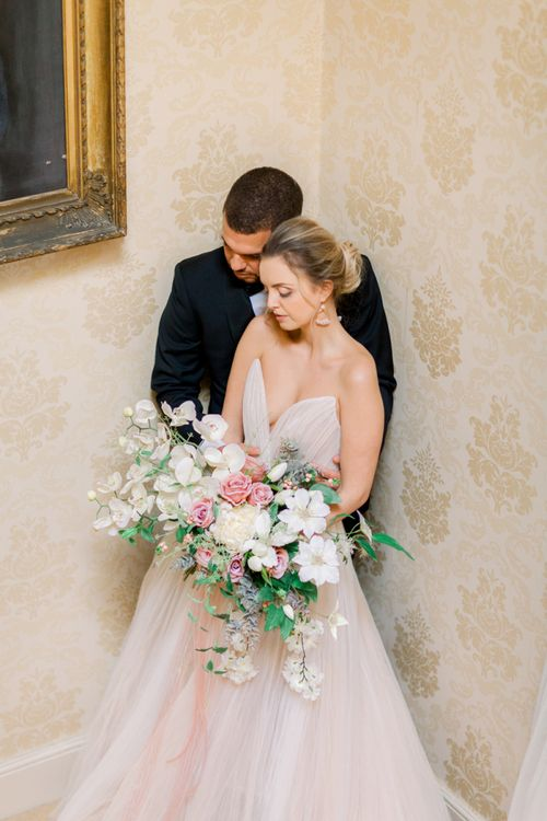 Bride and groom embracing in the stair well at Prestwold Hall wedding