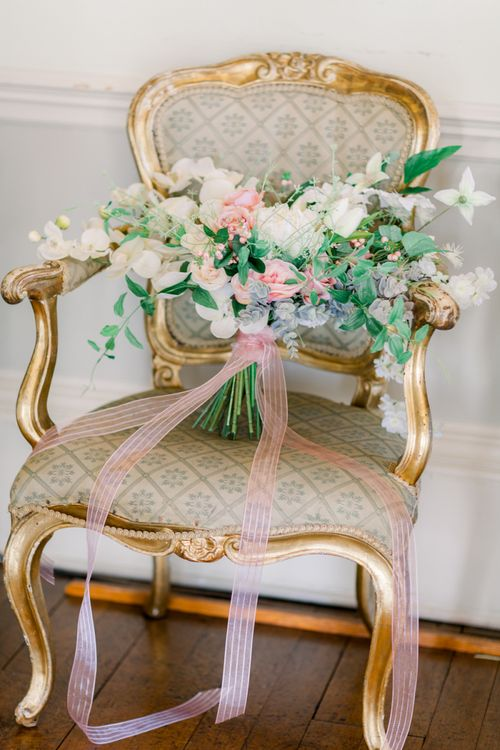 Bridal bouquet resting on a chair tied with ribbon