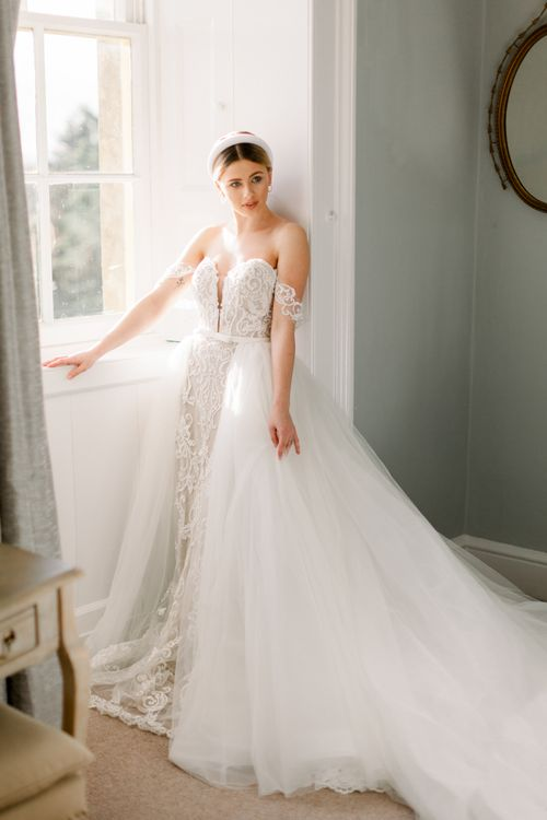 Bride in off the shoulder lace dress with detachable tulle overskirt