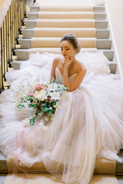 Bride in blush pink wedding dress sitting on the stairs at Prestwold Hall