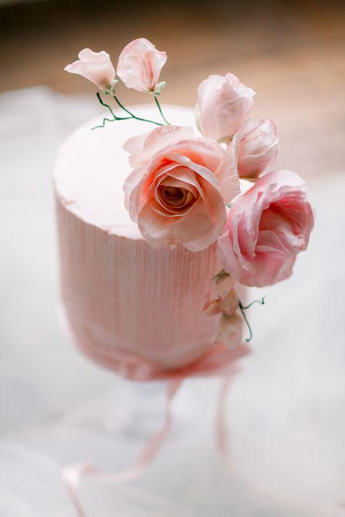Elegant pink frosting wedding cake with flower decor