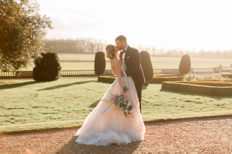 Golden Hour portrait with bride in tulle wedding dress and groom in black tie