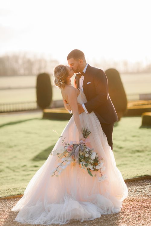 Groom in tuxedo kissing his bride in a romantic wedding dress at Prestwold Hall