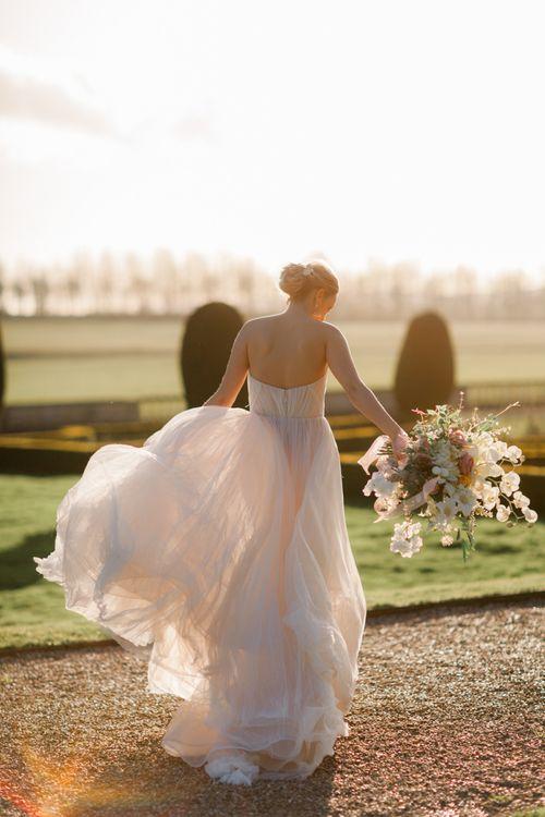 Golden hour portrait of bride in blush wedding dress