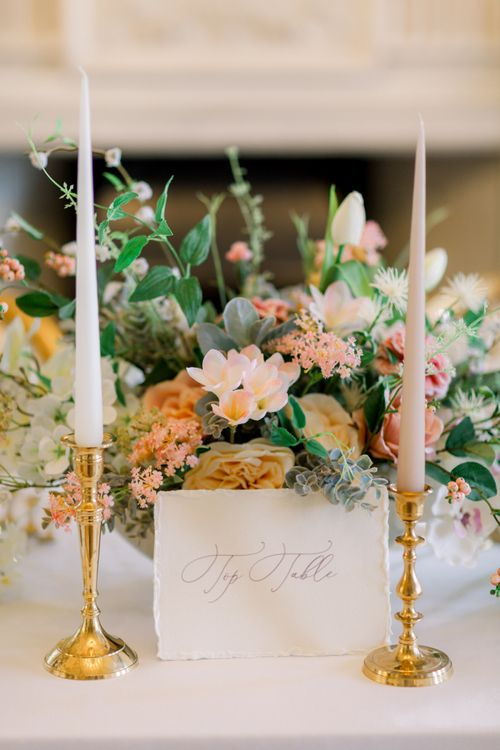 Top table calligraphy sign with gold candlesticks and peach flowers