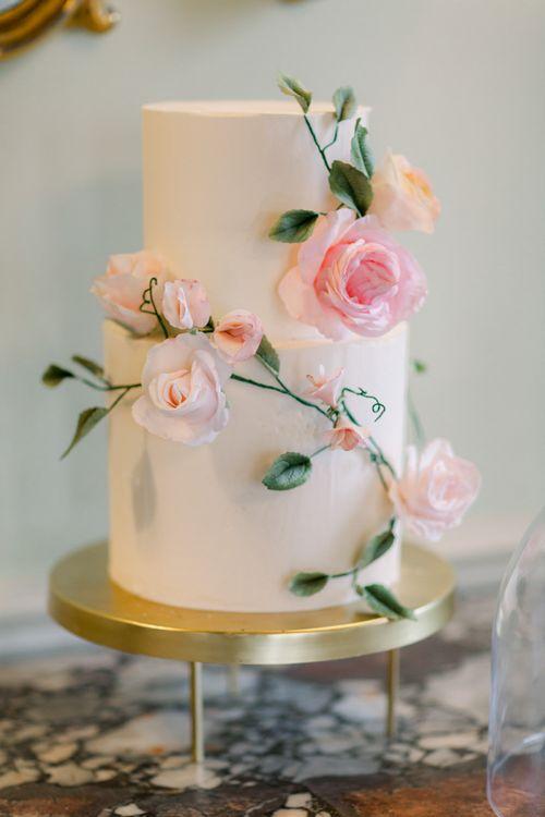 Elegant white wedding cake with pink flower decor