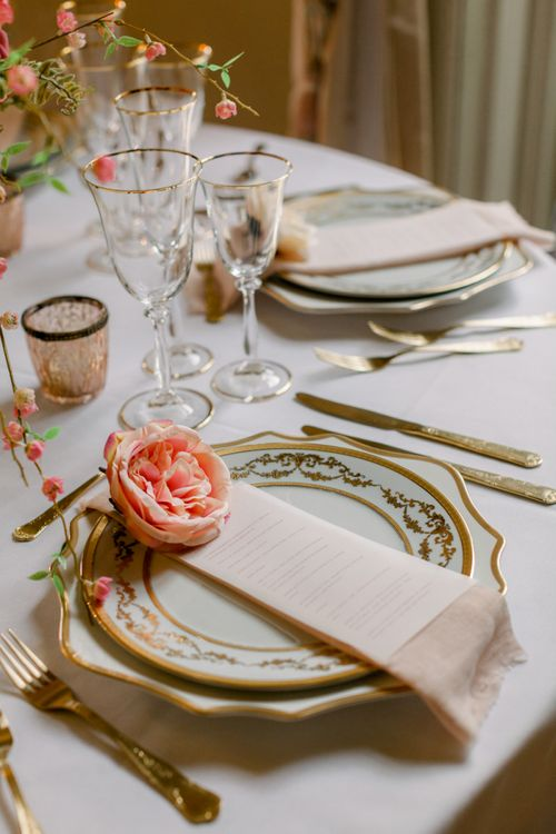 Place setting with ornate tableware and individual flower head
