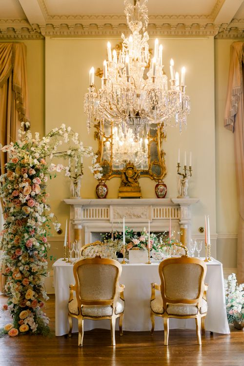 Sweetheart table at Prestwold Hall with ornate chandelier and fireplace