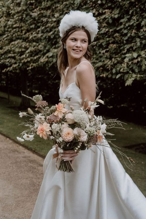 Bride in Emma Beaumont Wedding Dress and Headdress Holding a Peach and White Wedding Bouquet