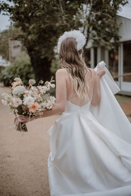 Bride in Spaghetti Strap Wedding Dress Holding a Blush Pink and White Bouquet