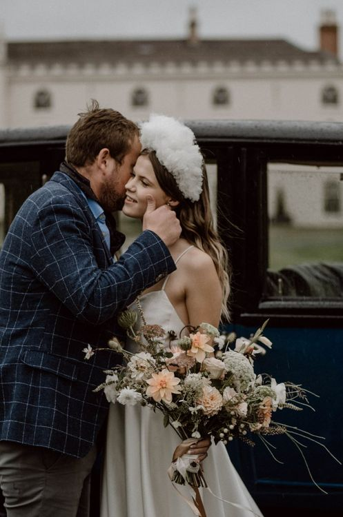 Groom in Blue Check Jacket Kissing His Bride with  White Headdress