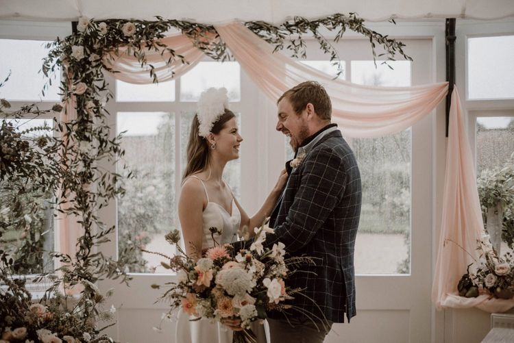 Bride Emma Beaumont Wedding Dress with Straps and Groom in Blue Check Suit Jacket Laughing at the Altar