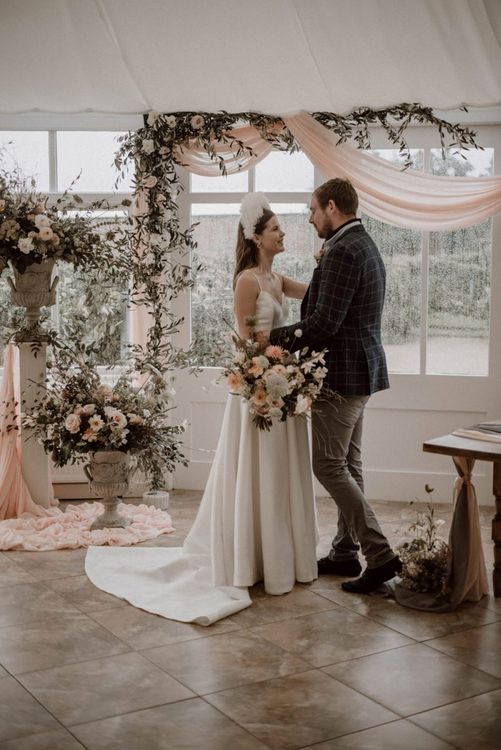 Bride and Groom Standing at the Flower Filled Altar with Pink Drapes