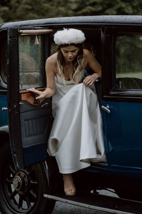 Bride in Emma Beaumont Wedding Dress and Headdress Getting out Of the Vintage Wedding Car