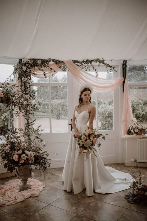 Bride in Emma Beaumont Wedding Dress with Straps Standing at the Flower and Drapes Covered Altar
