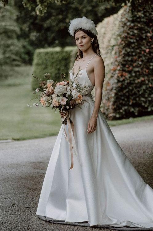 Stylish Bride in Emma Beaumont Wedding Dress with Thin Straps Holding a Peach and White Wedding Bouquet