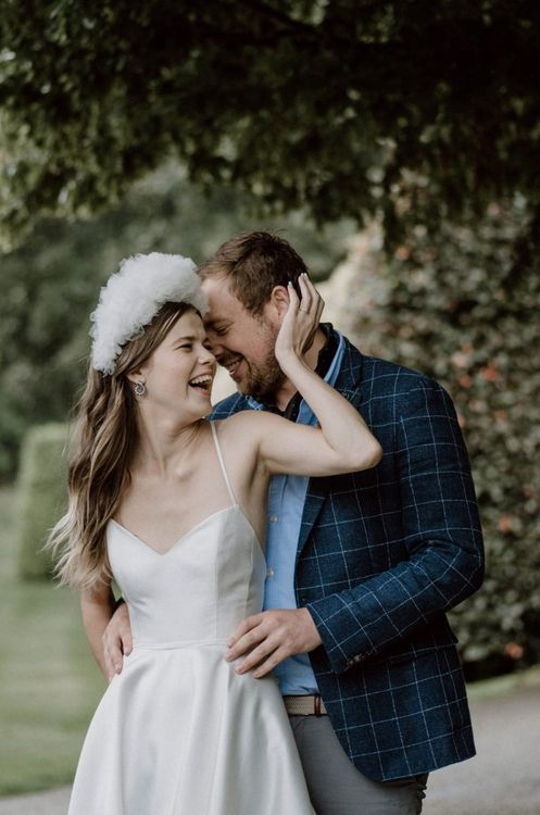 Groom in Blue Check Blazer Embracing His Bride in an Emma Beaumont Wedding Dress