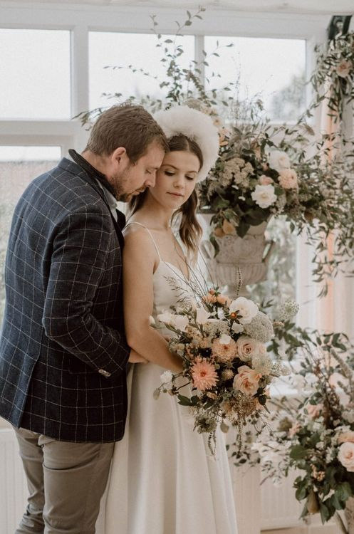 Groom in Blue Checked Blazer Embracing His Bride in an Emma Beaumont Silk Wedding Dress at the Floral Altar
