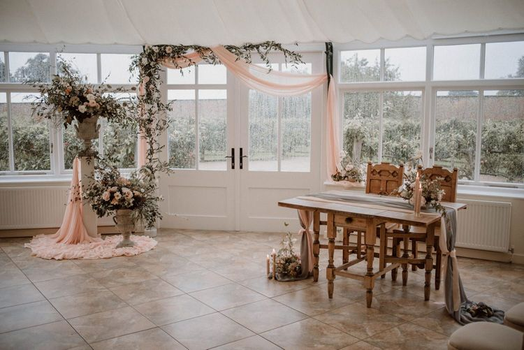 Combermere Abbey Glasshouse Ceremony Room with Draped Altar and Romantic Floral Arrangements