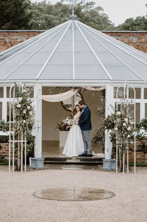 Bride and Groom Standing at the Entrance to Combermere Abbey's Glasshouse