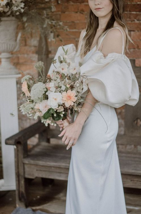 Bride in Puffed Sleeve Wedding Dress Holding a Peach and White Wedding Bouquet