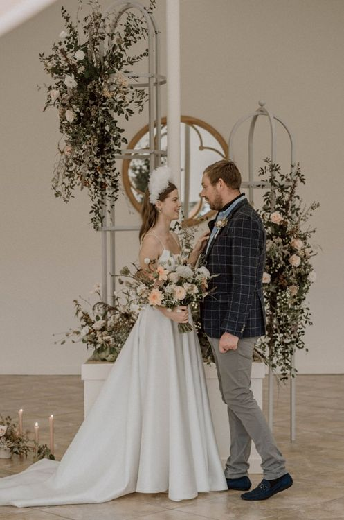 Bride and Groom Standing Next to a Pretty Floral Arrangement