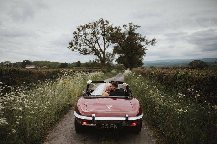 Bride and Groom In Red Vintage Car