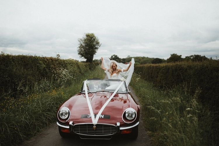 Bride in Emma Beaumont Wedding Dress Sits on Convertible Wedding Car While Groom Drives Down a Country Lane